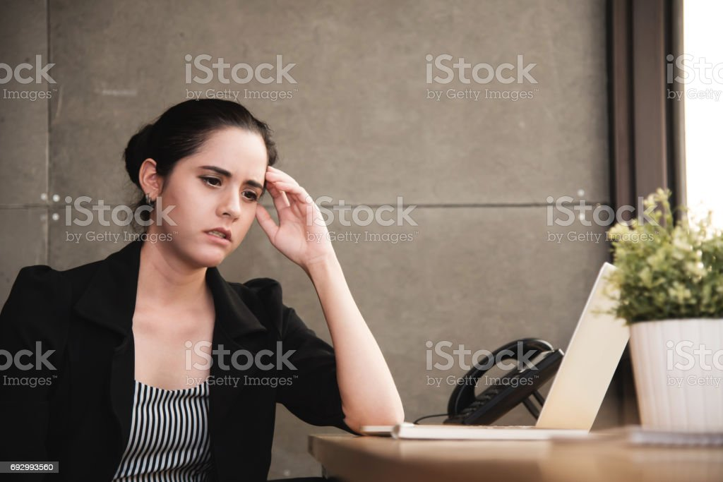 Businesswoman having headache from overwork at the office. stock photo