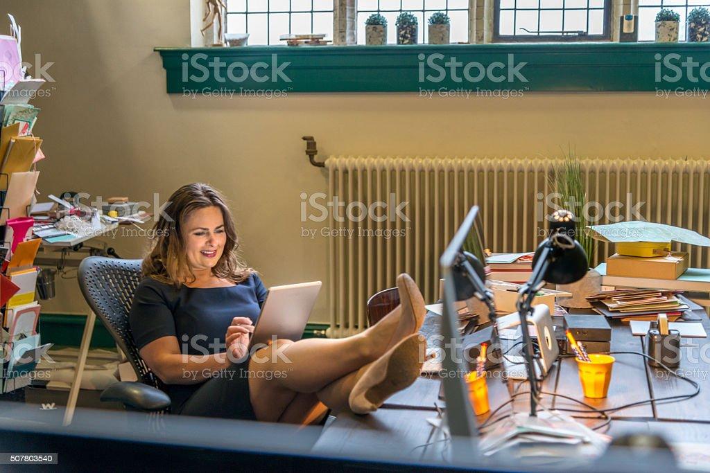 Businesswoman having internet break in office stock photo