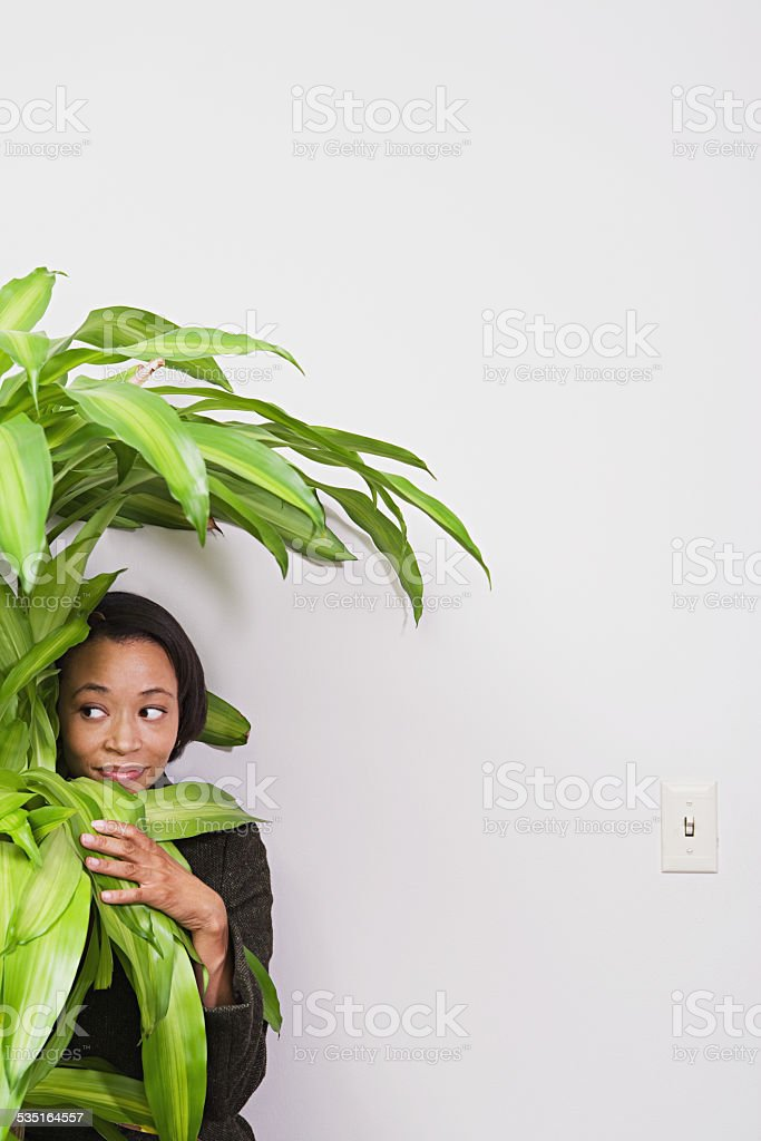 Businesswoman hiding behind office plant stock photo