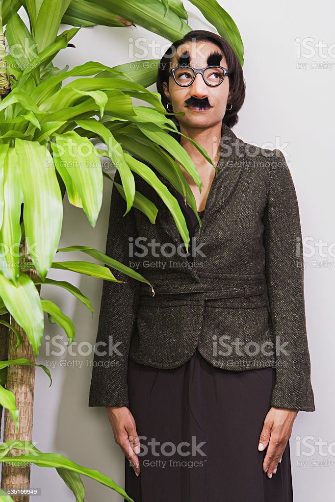 Businesswoman hiding behind plant wearing disguise stock photo
