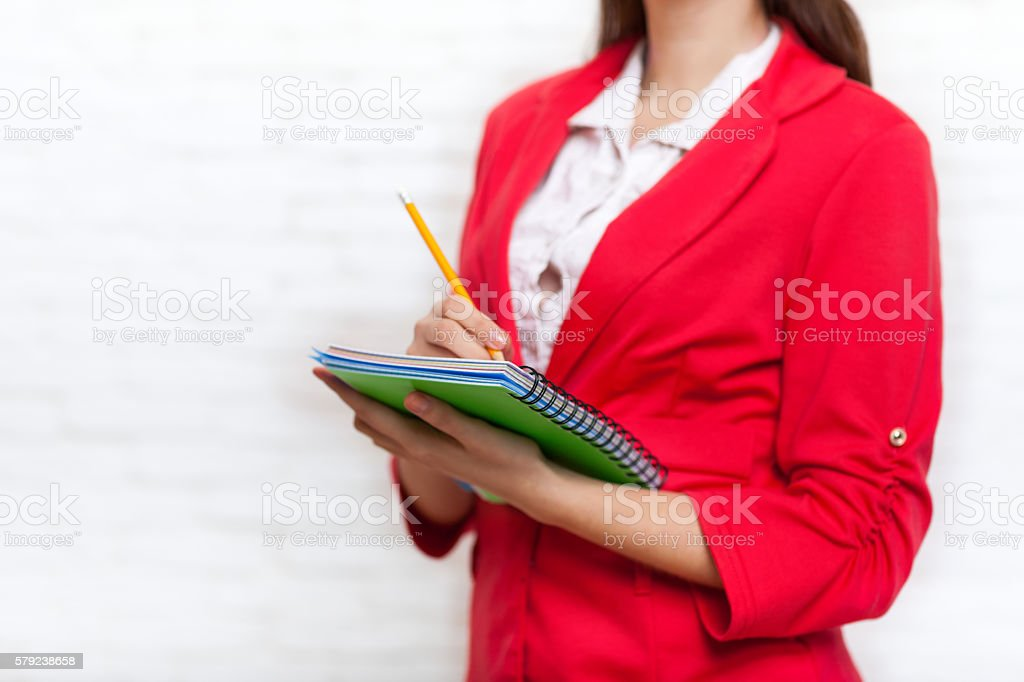 Businesswoman hold notebook pencil write wear red jacket stock photo