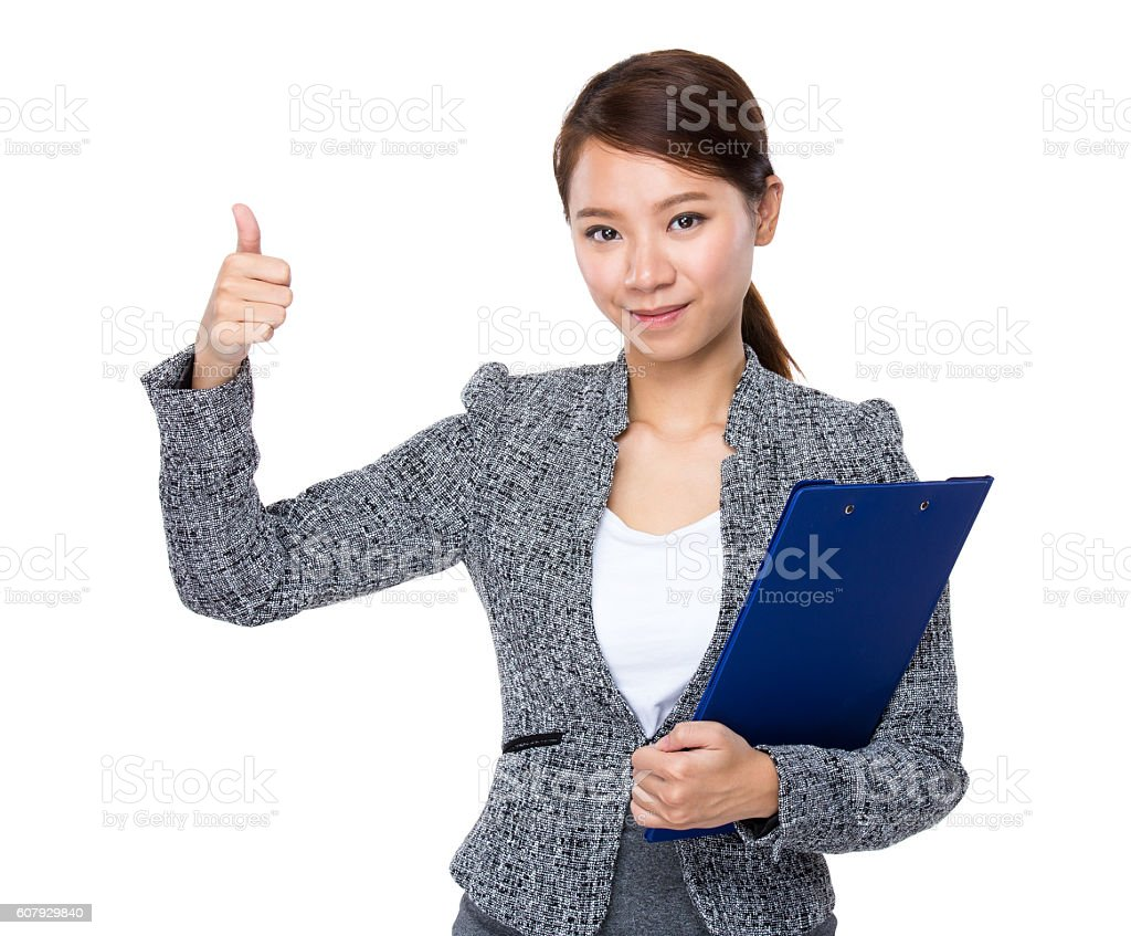 Businesswoman holding a clipboard and giving thumbs up stock photo
