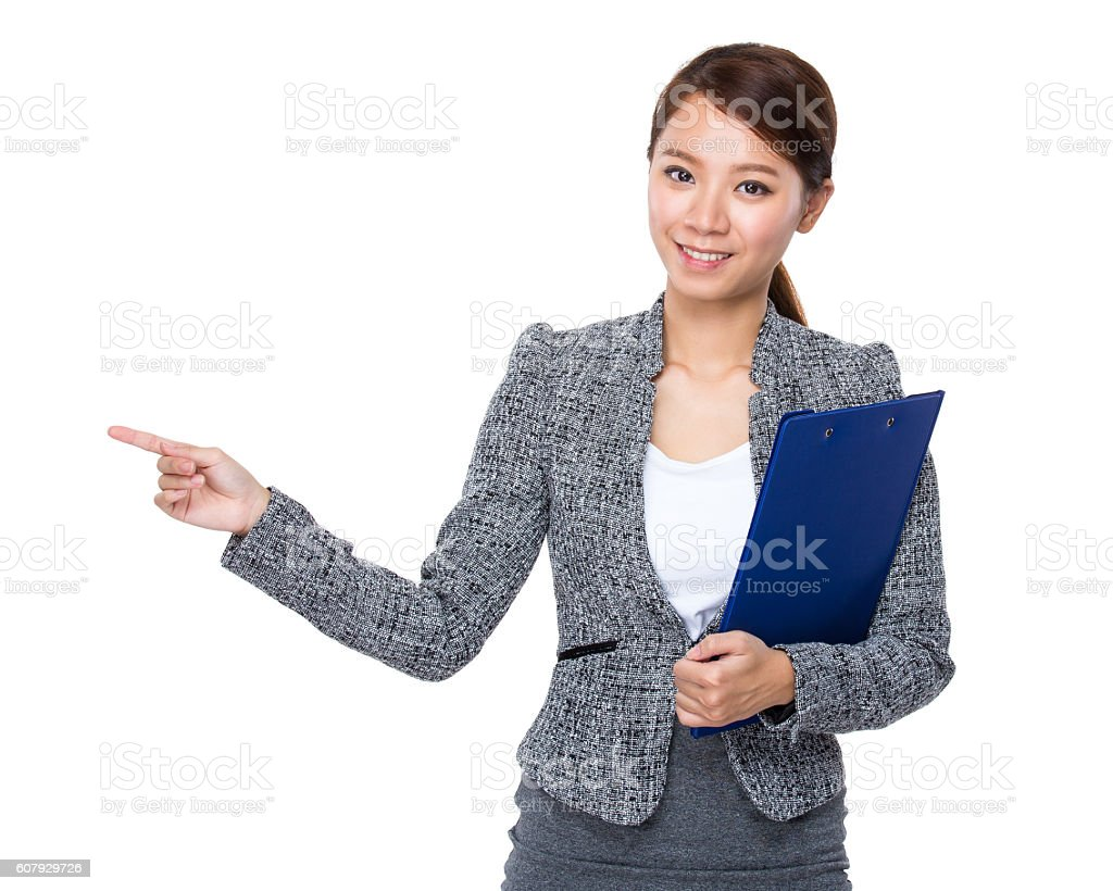 Businesswoman holding a clipboard and pointing stock photo