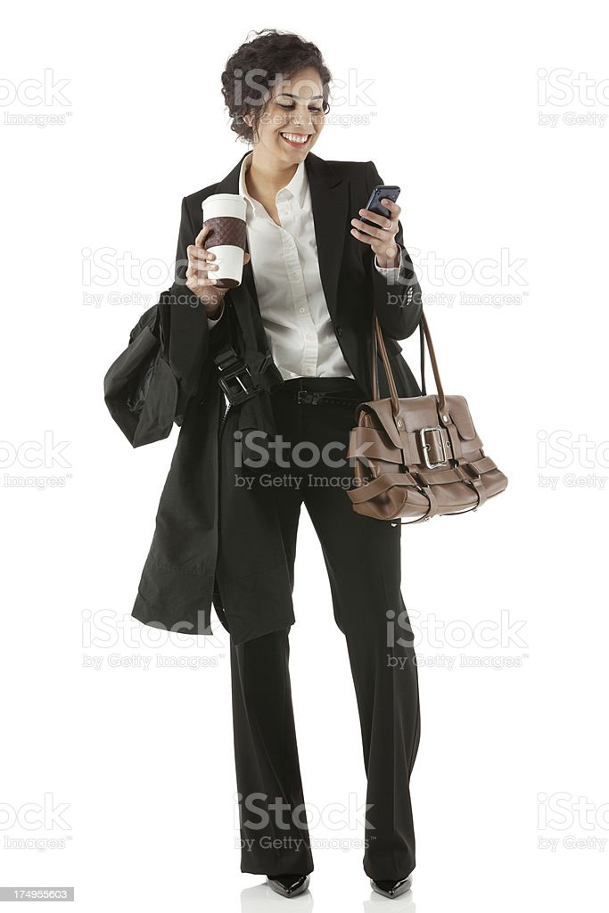 Businesswoman holding a disposable cup and using mobile phone royalty-free stock photo