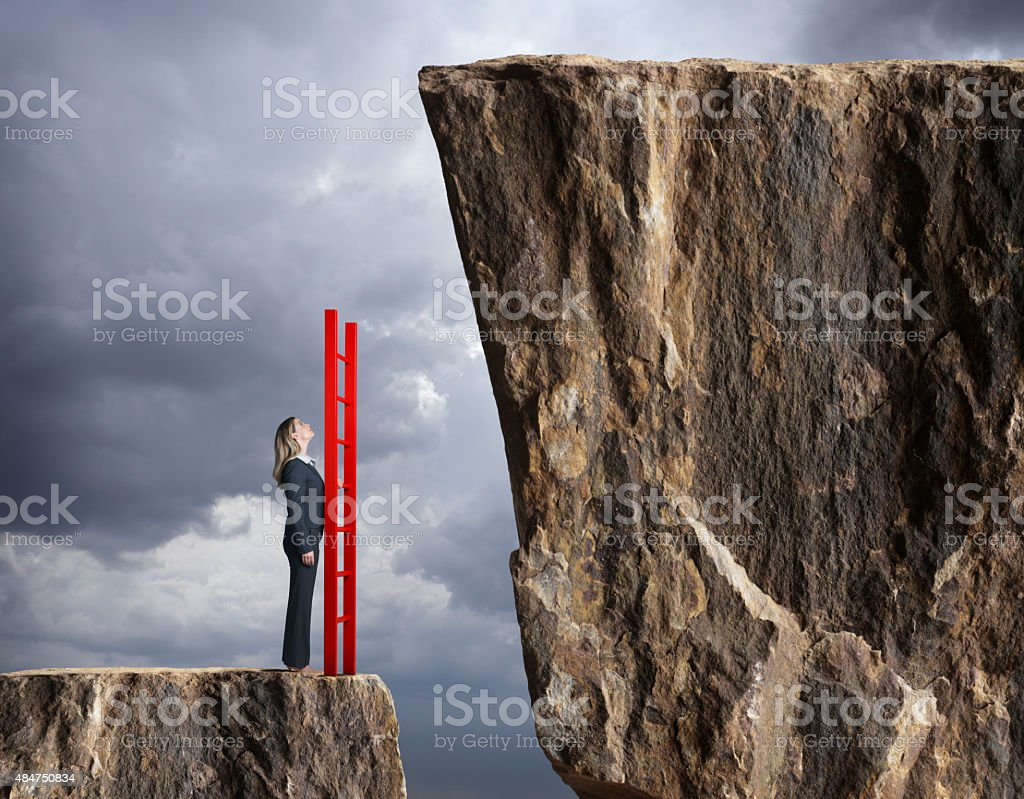 Businesswoman holding a ladder looks up towards higher level stock photo