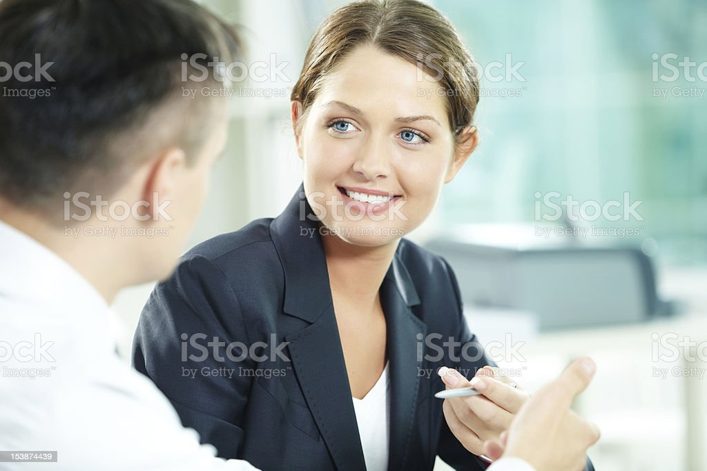 Businesswoman holding a pen and interacting with a man royalty-free stock photo
