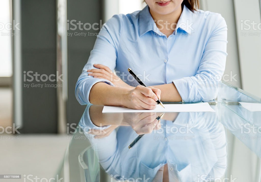 Businesswoman holding a pen and writing stock photo