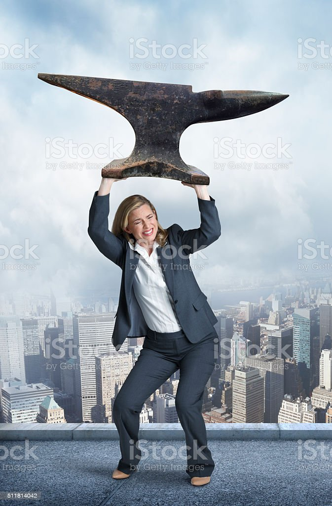 Businesswoman Holding An Anvil Over Her Head In Big City stock photo