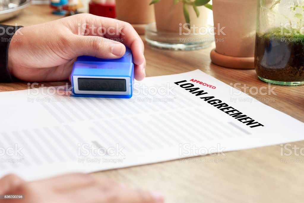 Businesswoman holding an approved rubber stamp with loan agreement document on wooden desk. stock photo
