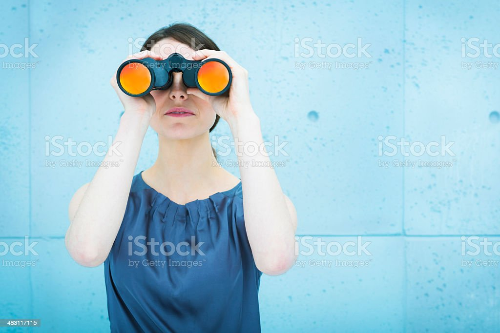 Businesswoman holding binoculars stock photo