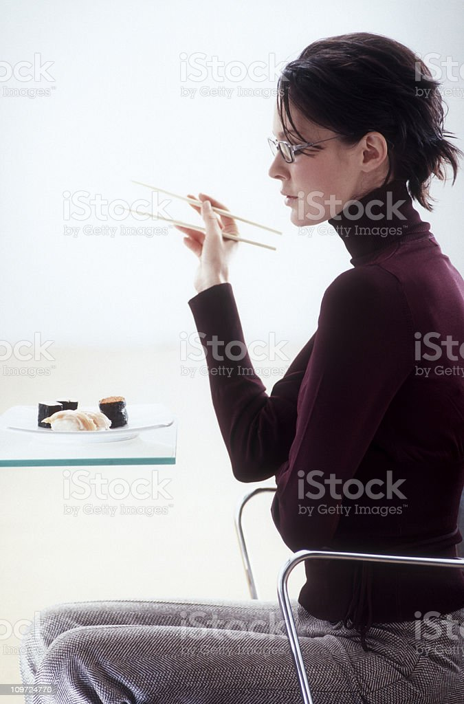 Businesswoman holding chopsticks and looking at Sushi Plate royalty-free stock photo