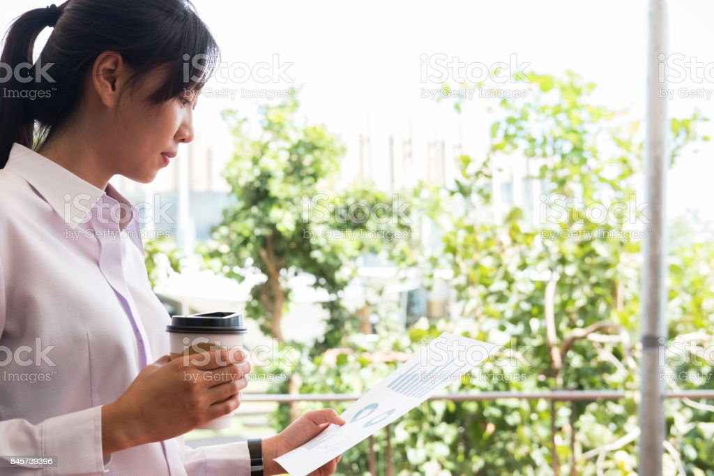 businesswoman holding coffee cup & financial summary graph outside office building. beautiful young asian woman with tea analyzing investment charts outdoors. business people with disposable paper cup checking marketing data stock photo