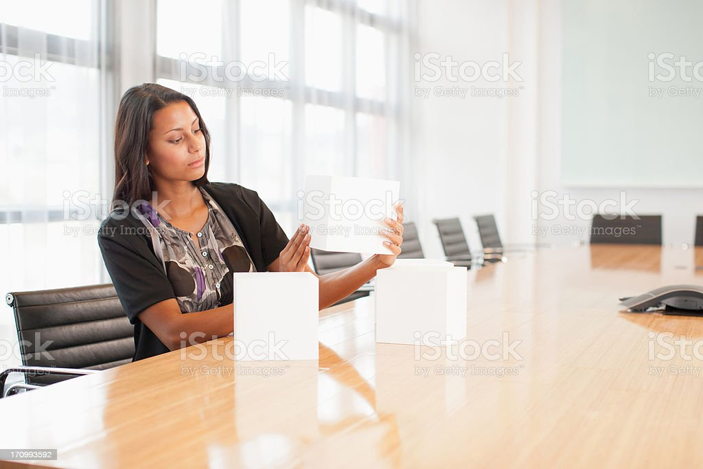 Businesswoman holding cube in conference room stock photo