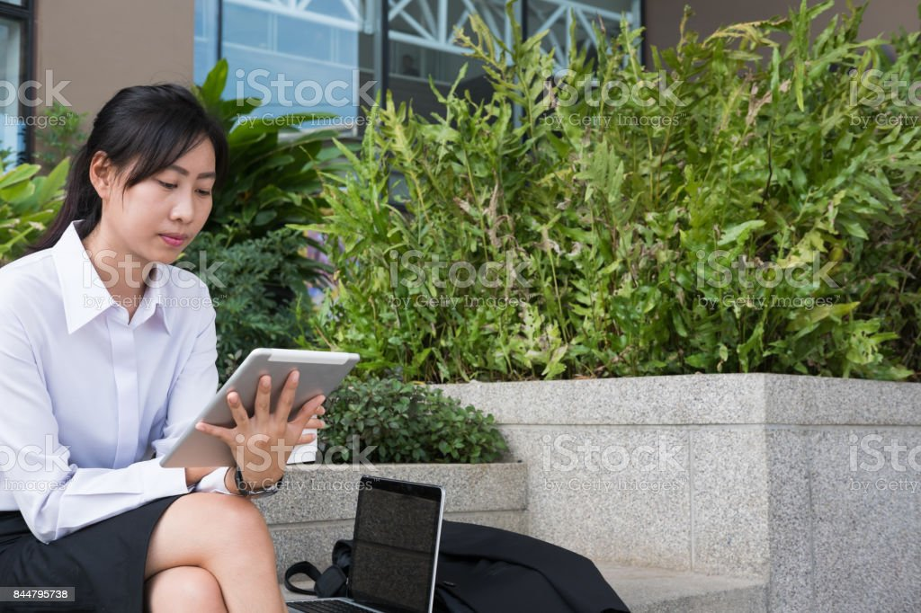 businesswoman holding digital tablet & coffee outside office building. beautiful young asian woman with tea sitting outdoors. female adult with disposable paper cup have a break in business area stock photo