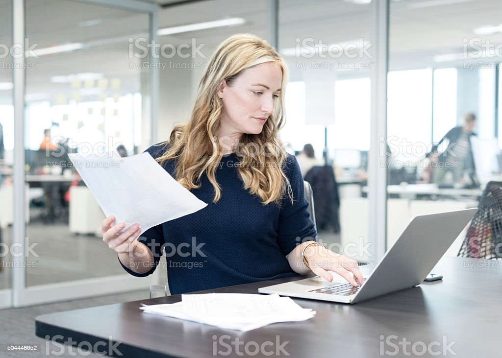 Businesswoman holding document and using laptop in modern office stock photo