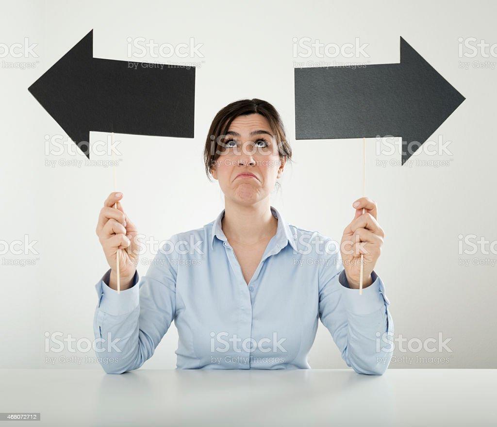 businesswoman holding double arrow sign stock photo