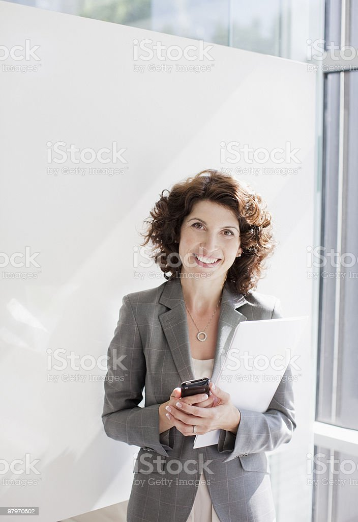 Businesswoman holding file and cell phone royalty-free stock photo