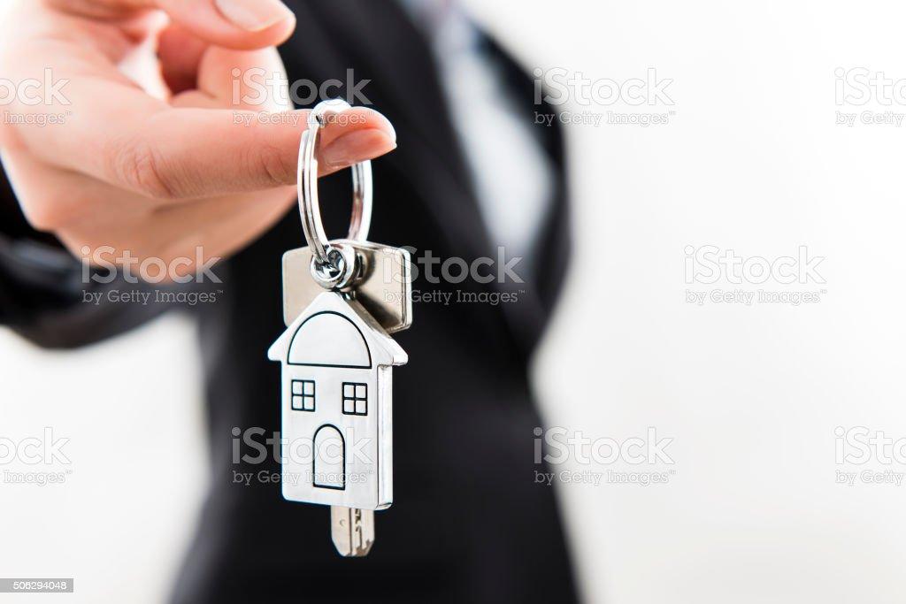 Businesswoman holding house key stock photo