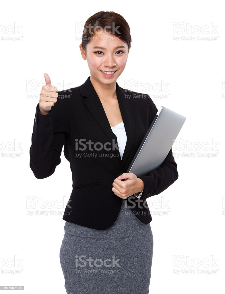 Businesswoman holding laptop and giving thumbs up stock photo