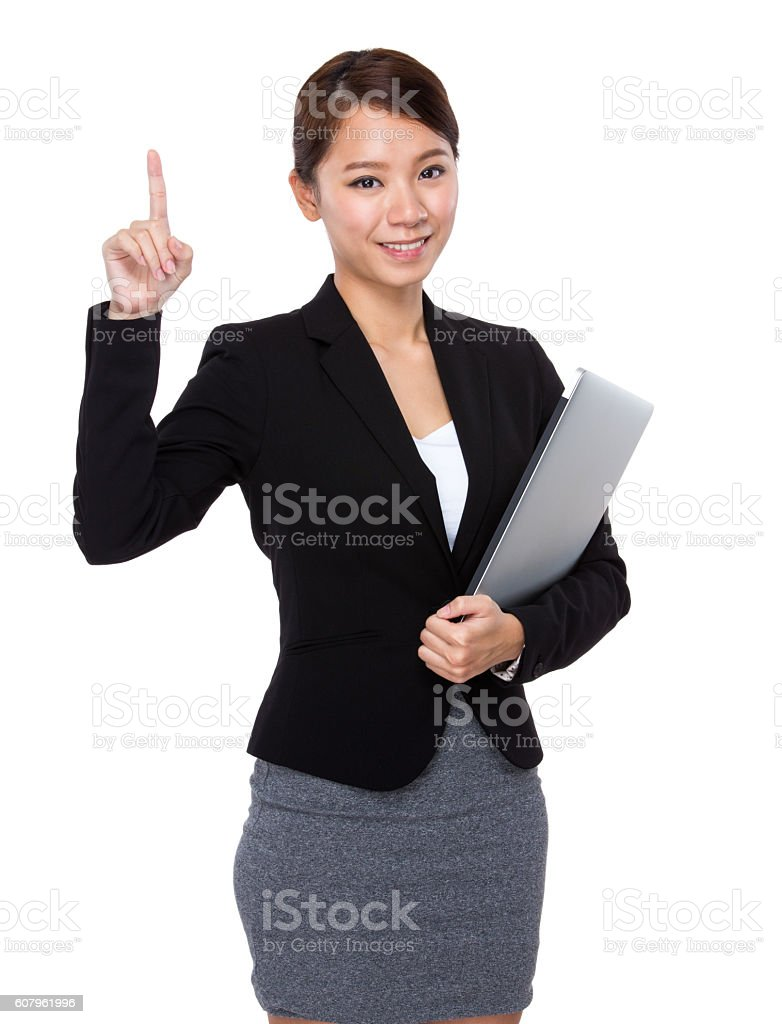 Businesswoman holding laptop and pointing stock photo