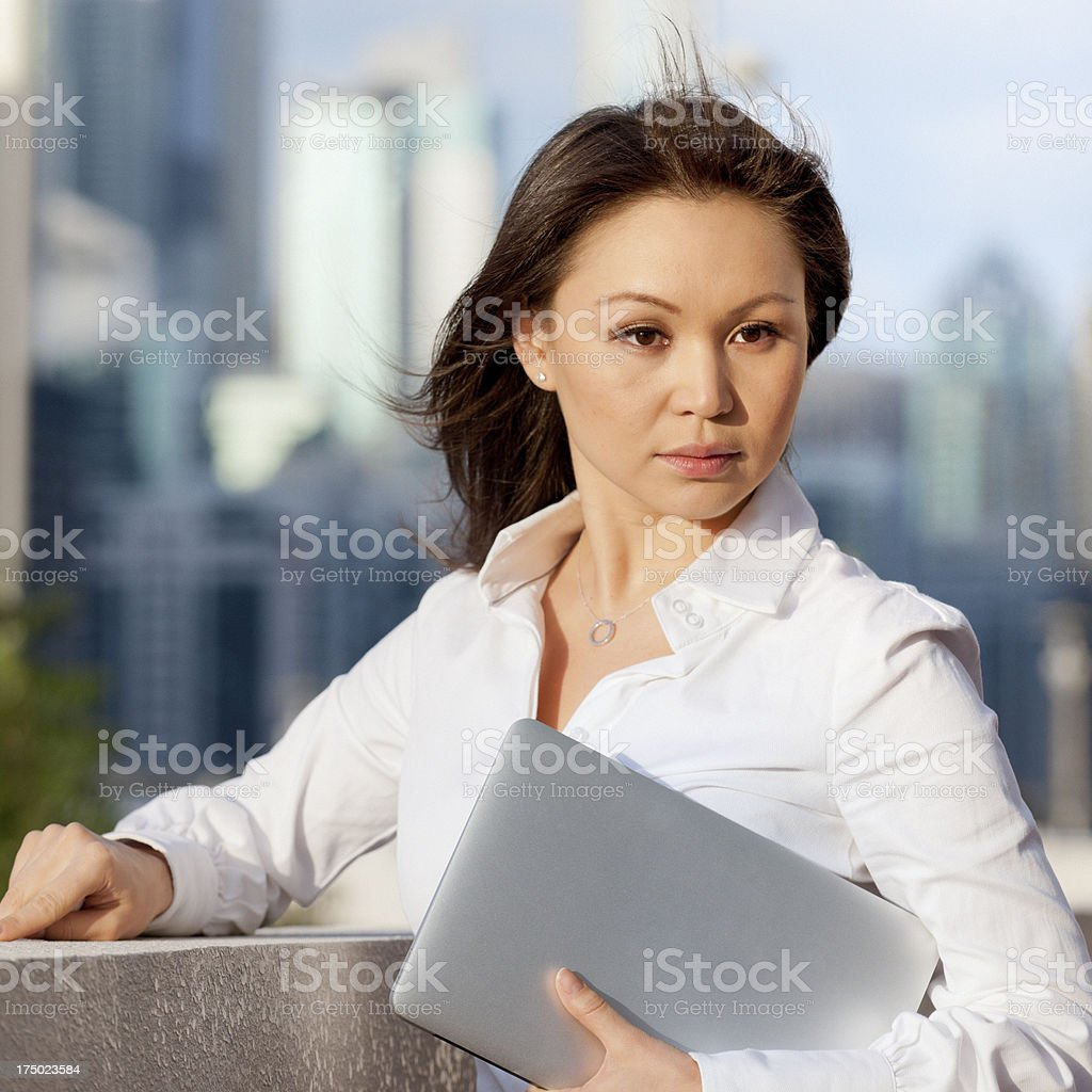 businesswoman holding laptop in downtown district stock photo