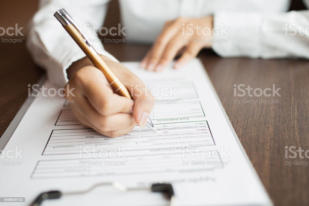 Businesswoman holding pen and reading document stock photo