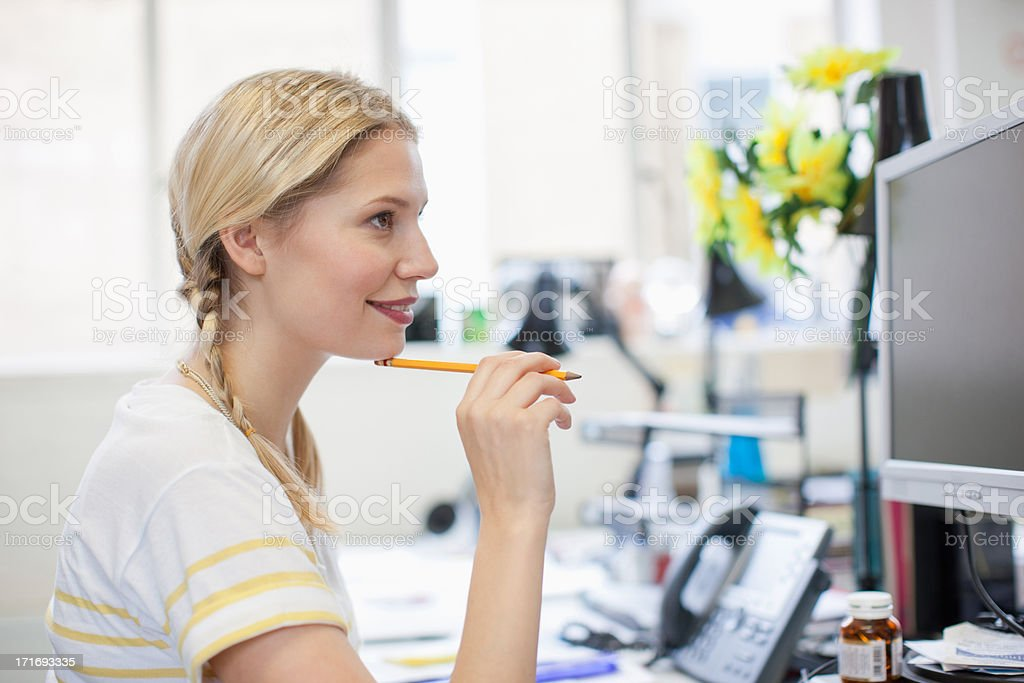 Businesswoman holding pencil and looking at computer monitor stock photo