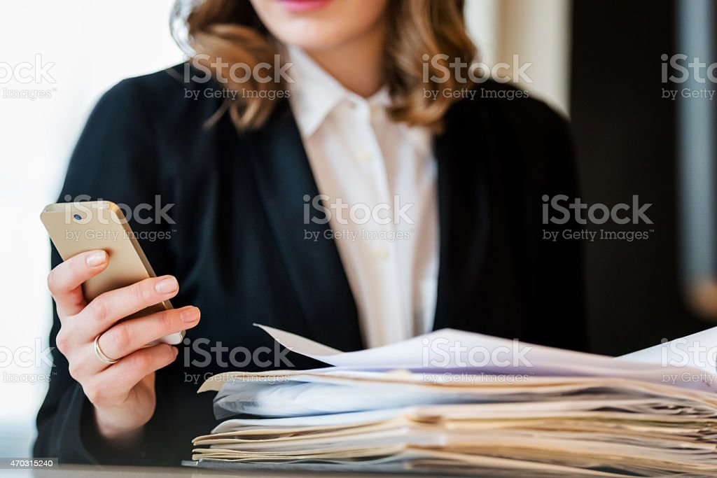 Businesswoman Holding Smart Phone While Sitting At Desk stock photo
