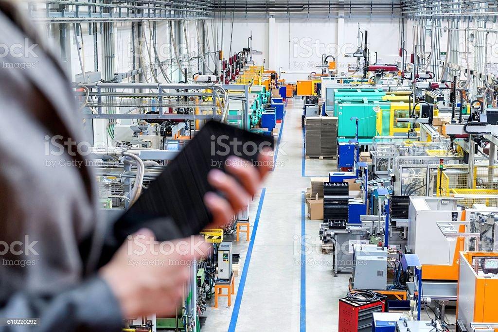 Businesswoman holding tablet, focus on robotic machines stock photo