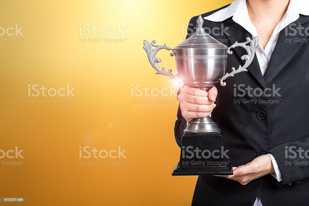 Businesswoman holding trophy award for success in business. gold stock photo