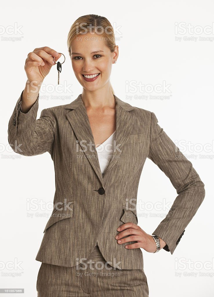 businesswoman holding up keys towards camera stock photo