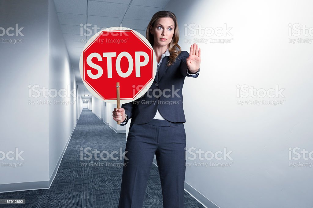 A businesswoman standing in a long hallway holding a stop sign.