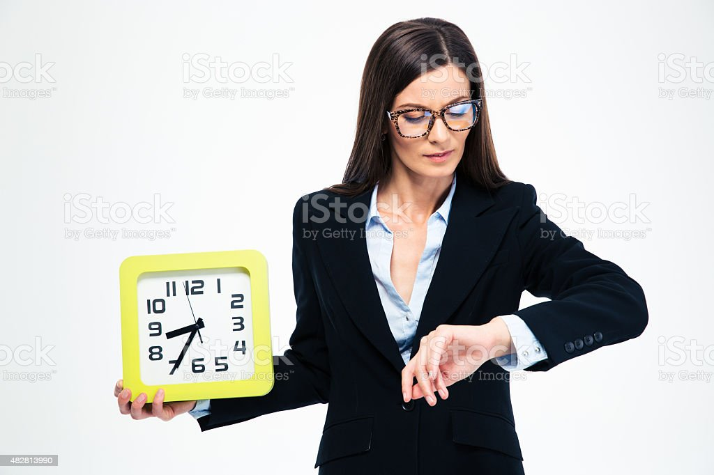 Businesswoman holding wall clock and looking on wristwatch stock photo