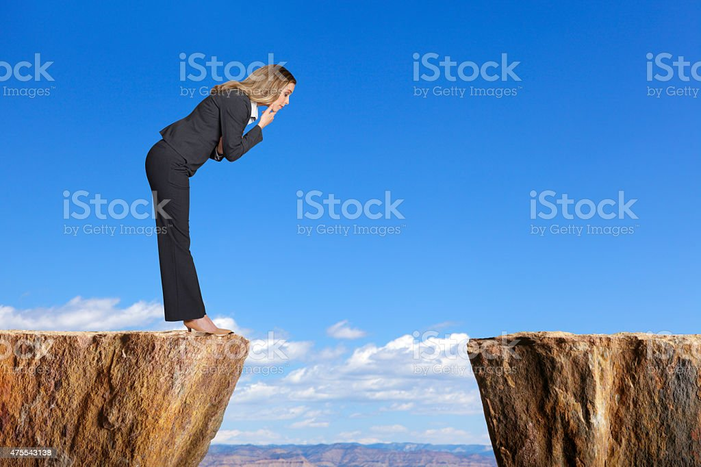 Businesswoman in a suit stares at space between two ledges stock photo