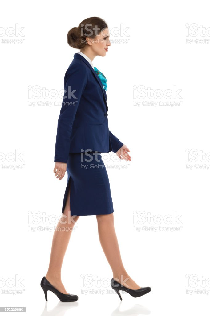 Businesswoman In Blue Suit Walking Side View stock photo