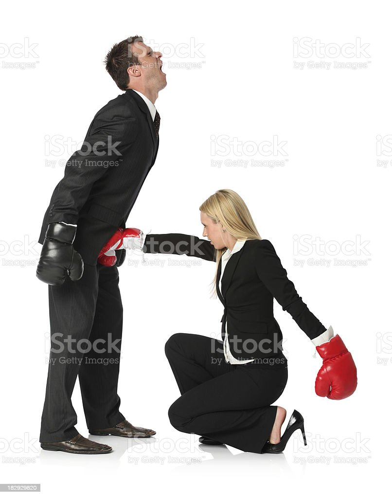 Businesswoman in boxing glove hitting on groin of businessman stock photo
