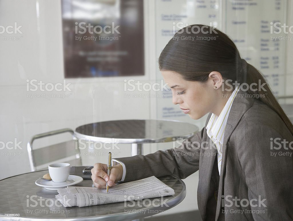 Businesswoman in cafeteria with newspaper royalty-free stock photo