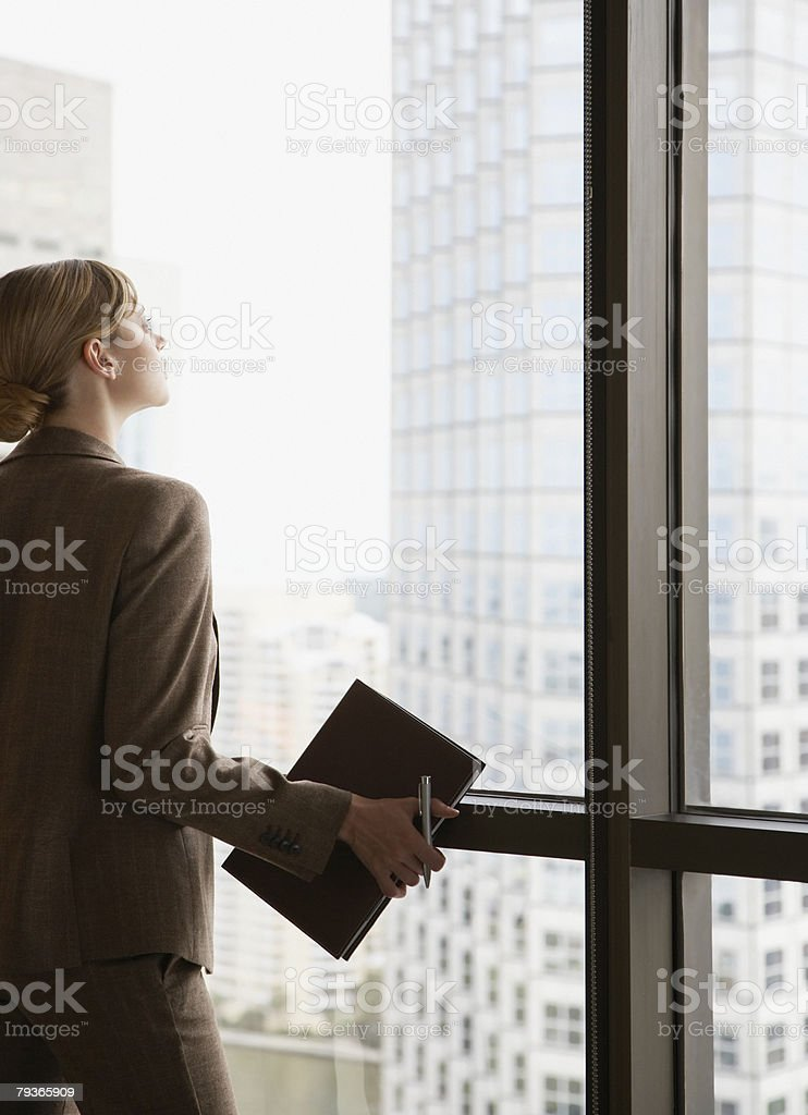 Businesswoman in corridor looking out large window royalty-free stock photo