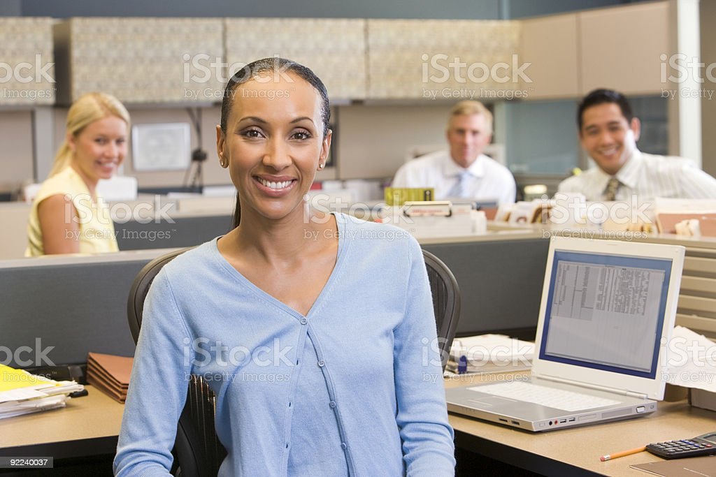 Businesswoman in cubicle stock photo