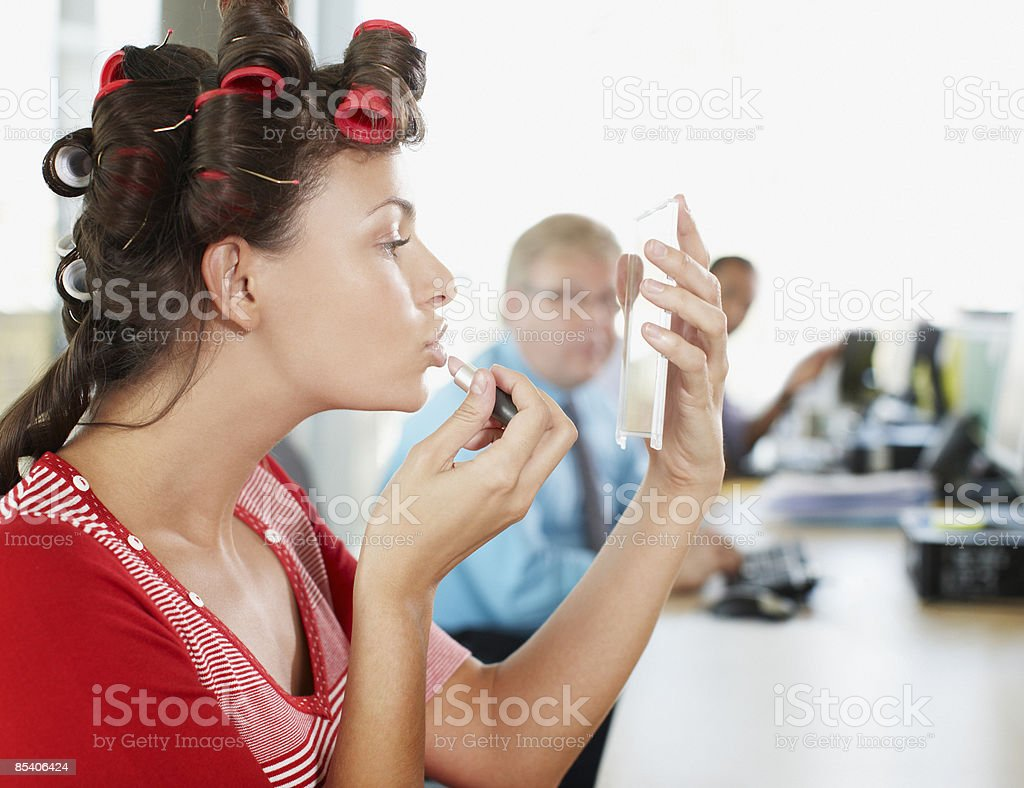 Businesswoman in curlers applying lipstick at desk royalty-free stock photo