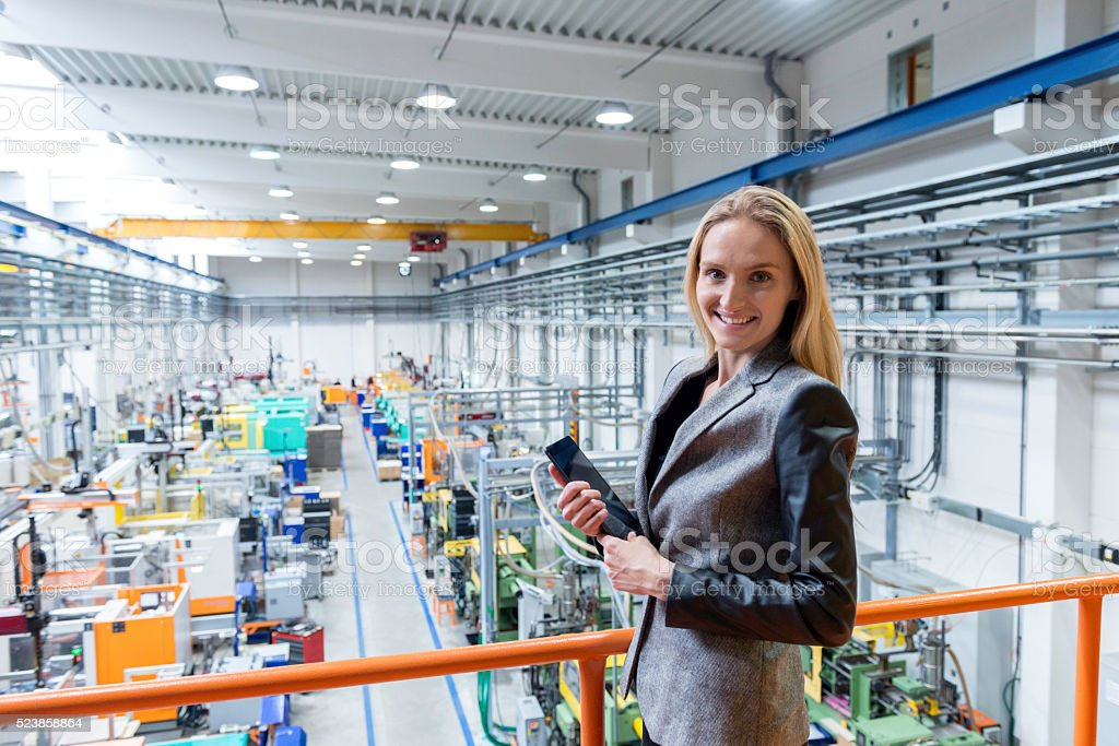 Businesswoman in factory working on digital tablet stock photo