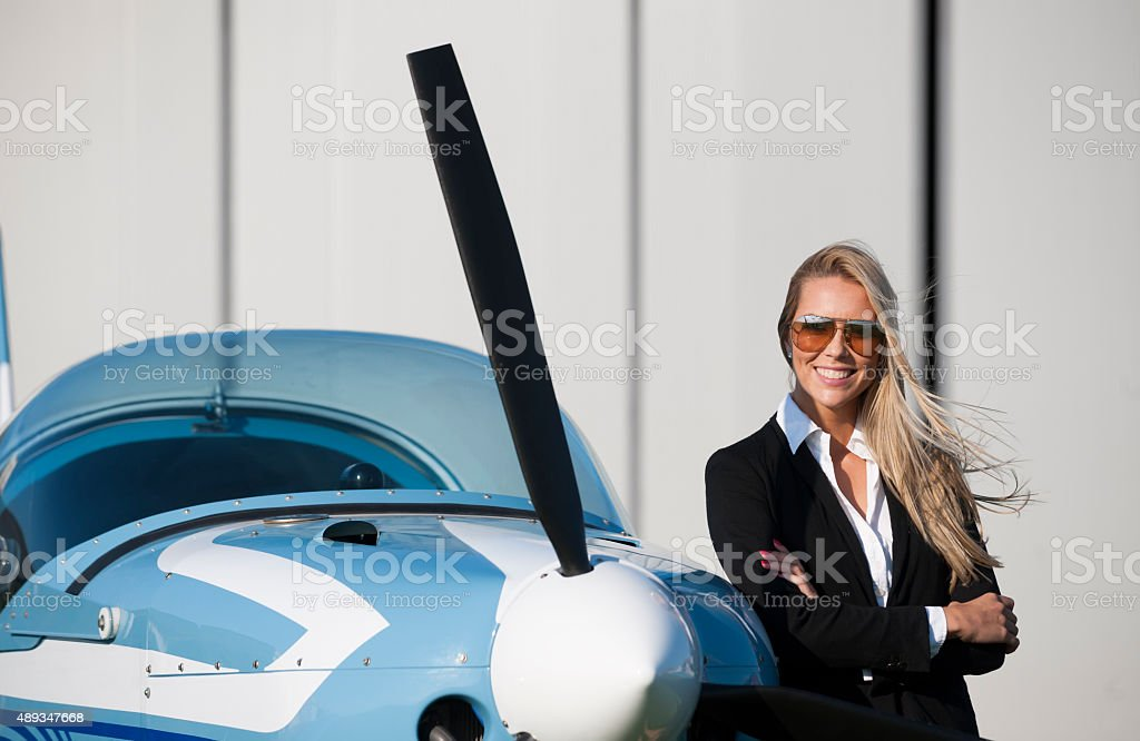 Businesswoman in front of privet jet airplane stock photo