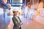 Businesswoman in hard-hat standing in factory