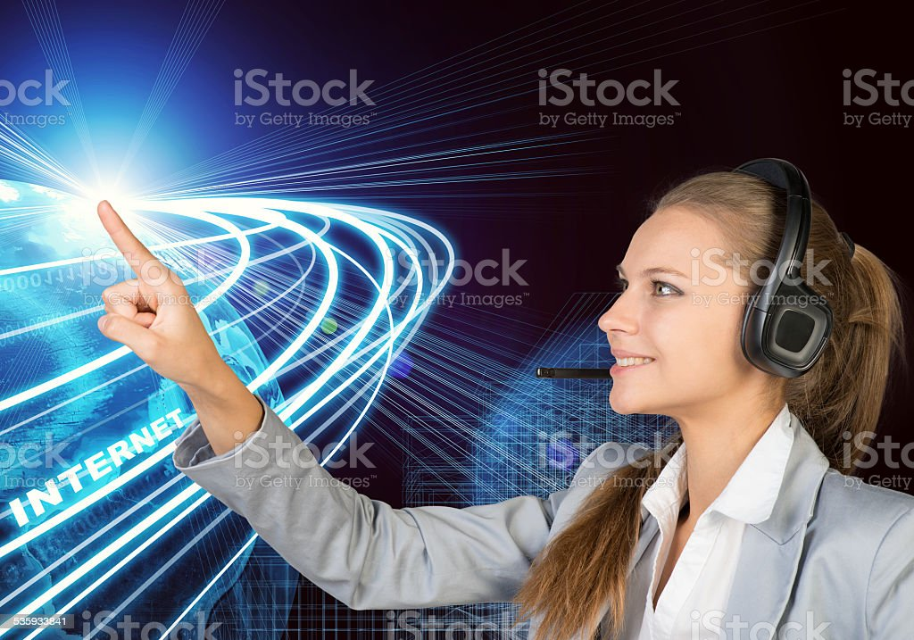 Businesswoman in headset touching or pressing something stock photo