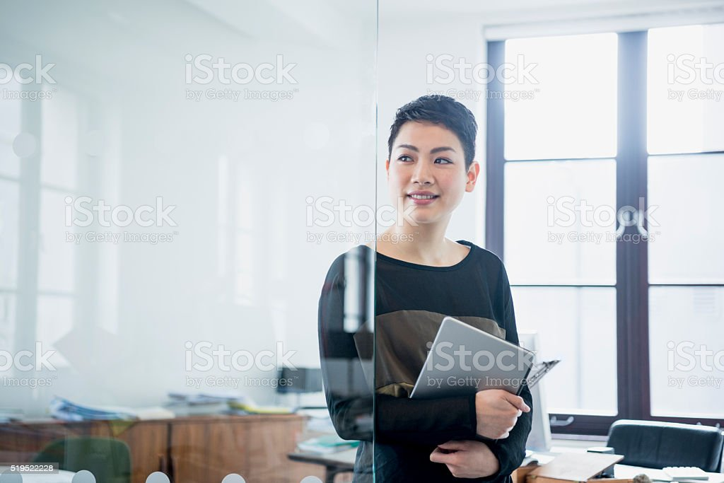Businesswoman in modern office looking away through partition stock photo