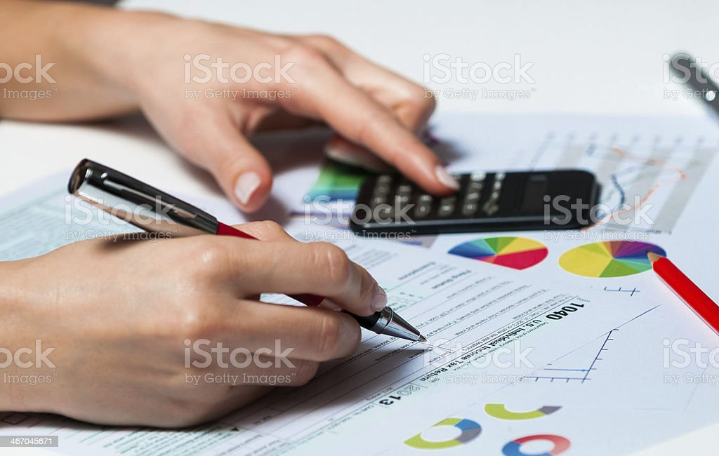 Businesswoman in office dealing with taxes finances and stock markets stock photo