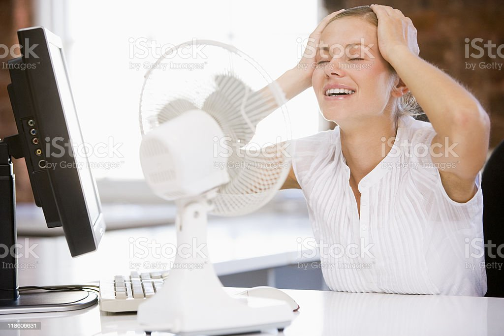 Businesswoman in office with fan cooling off stock photo