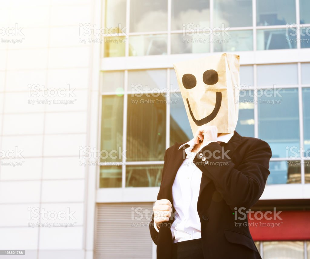 Businesswoman in smiling paper bag mask outside office building stock photo