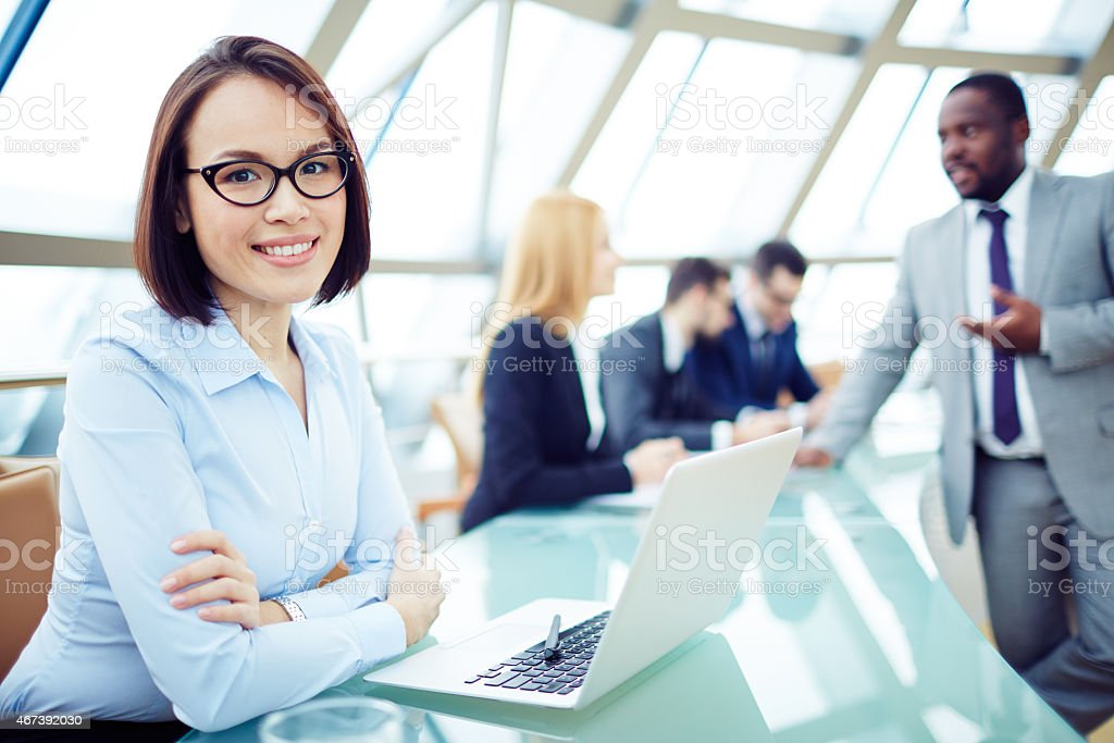 Businesswoman in smiling pose at desk stock photo