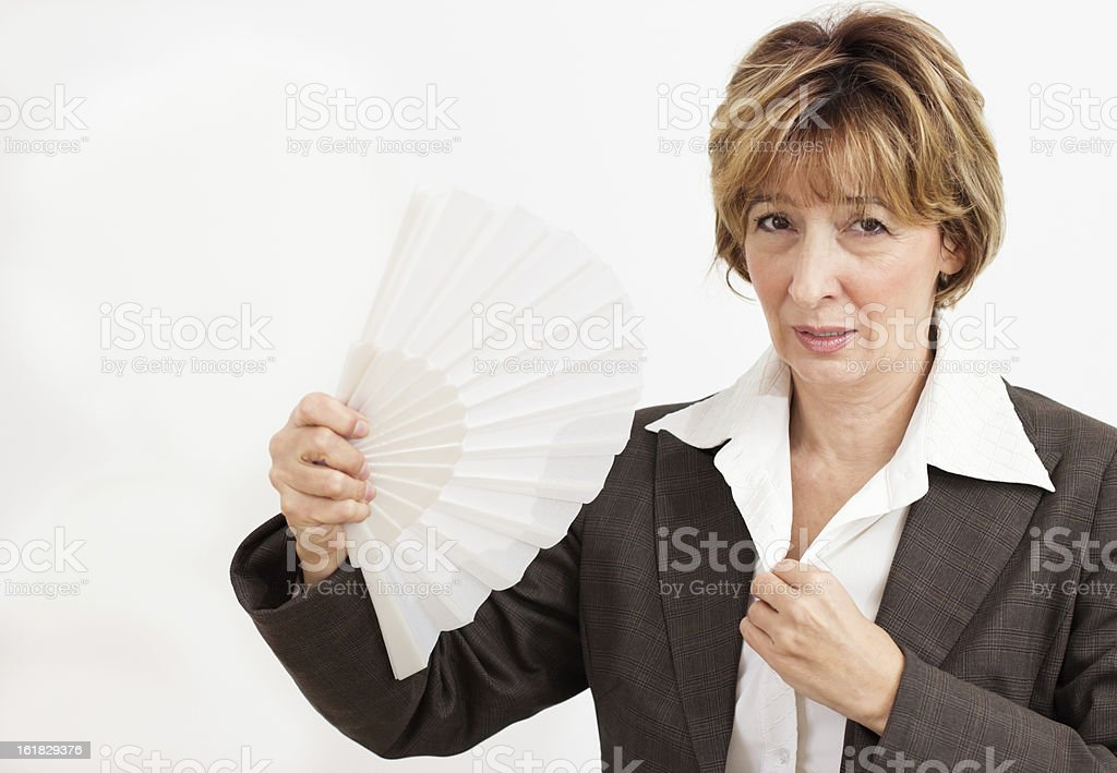 Businesswoman in suit fanning herself with a paper fan stock photo